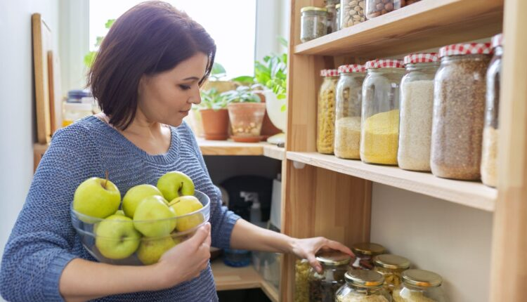 a woman carrying a bunch of apples inside the kitchen racks