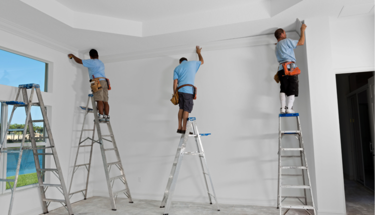 three men on the ladder making a crown molding