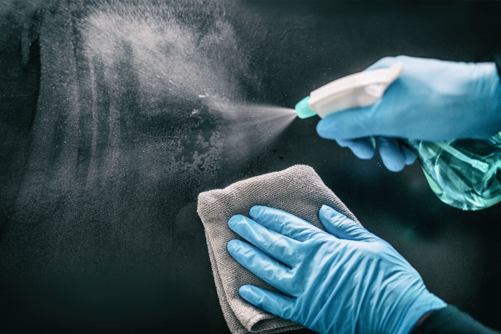 photo of hands with a gloves spraying the surface to clean