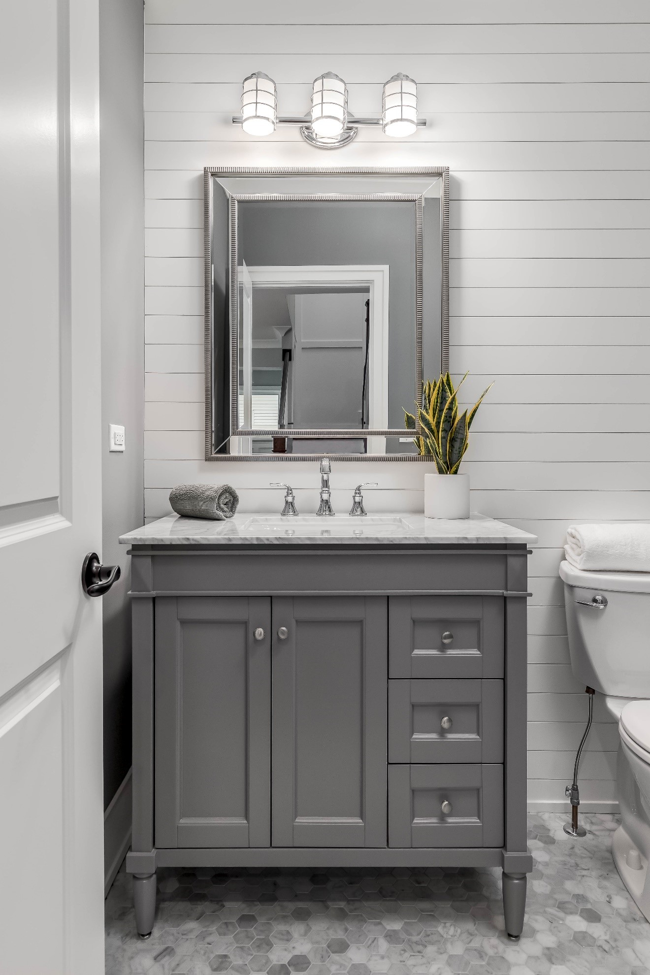 a white wall with mirror and gray drawer