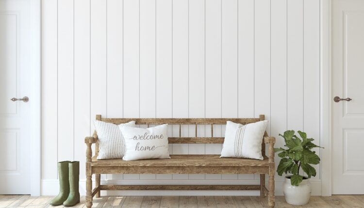 a white shiplap wall with a wooden chair and plant