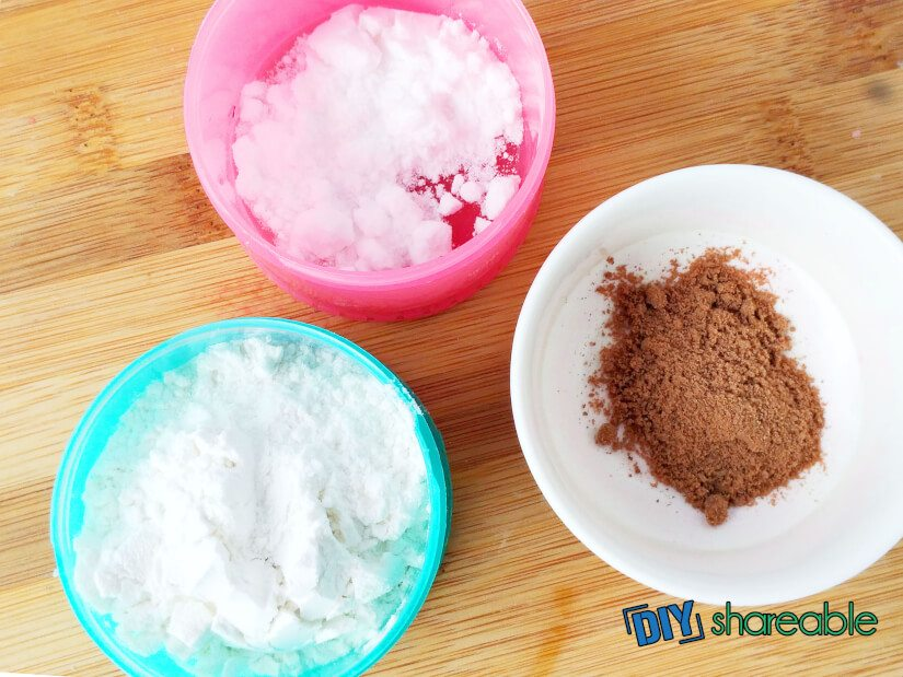 A white bowl with cocoa powder, a pink bowl with cornstarch, and a blue bowl with baby powder sitting on a wooden table.