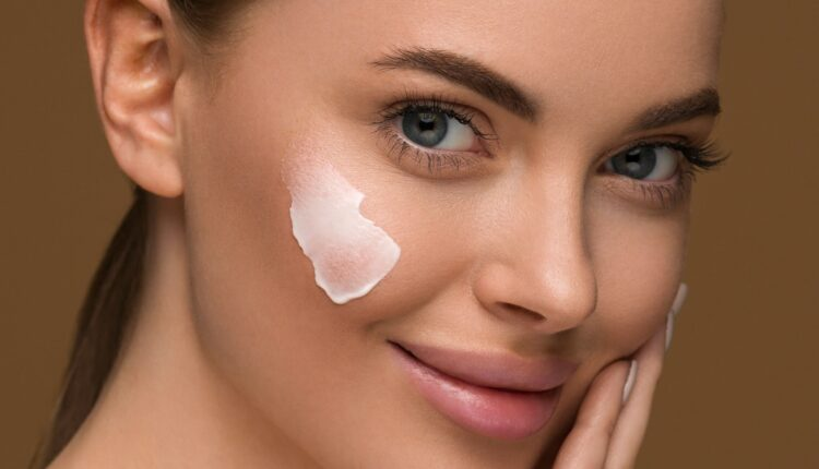 photo of a woman smiling with a moisturizer in her face