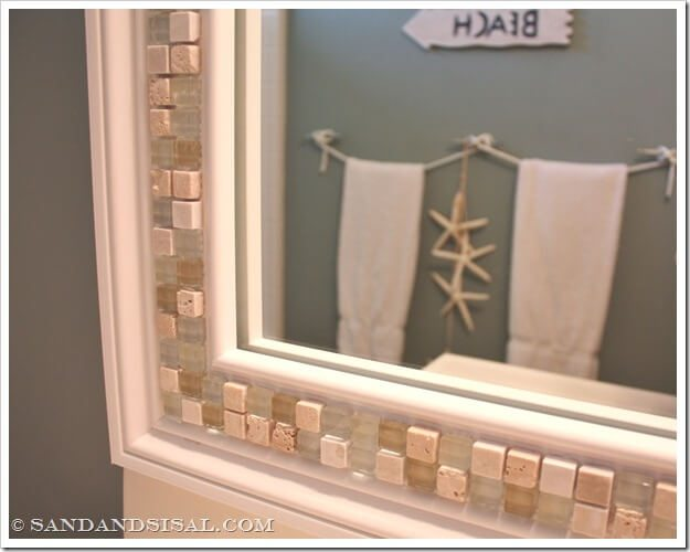 Decorative glass tiles give an ordinary mirror a new look in this half bath.