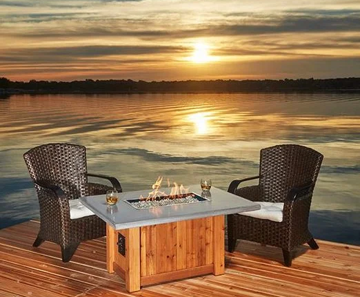 a photo of table and chairs with a sunset