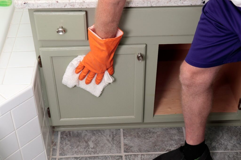 a man wiping the cabinet