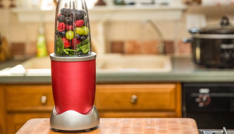 a red blender with a fruits in it