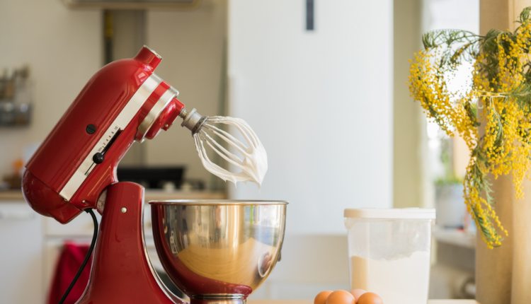 a red mixer with egg and flour on the background