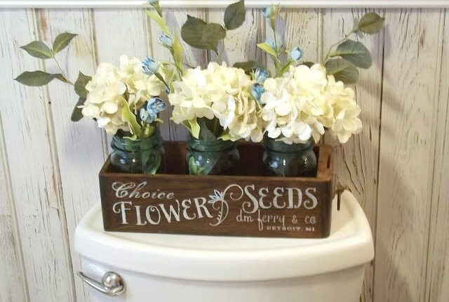 This is a cute box of flowers on a toilet