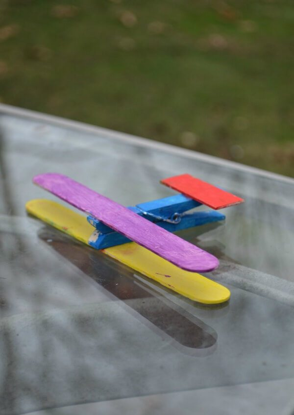 popsicle stick colored airplane with clothespin