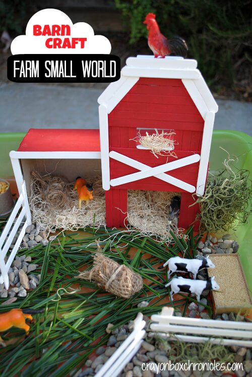 red and white popsicle stick barn with grass and toy animals