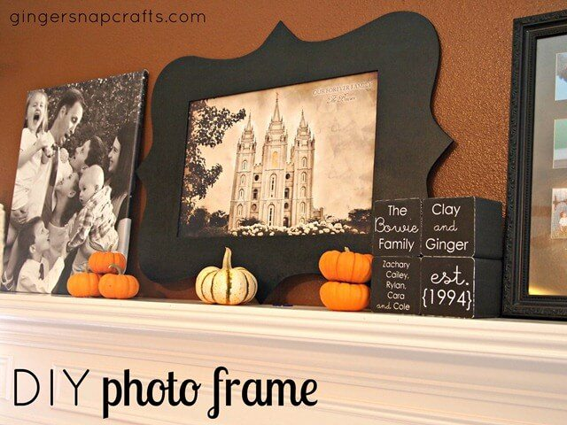 cut out black silhouette photo frame with pumpkins on fireplace ledge