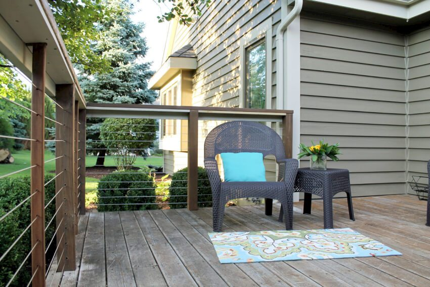 Beautiful cable wire deck railing installation with a blue cushion wicker chair