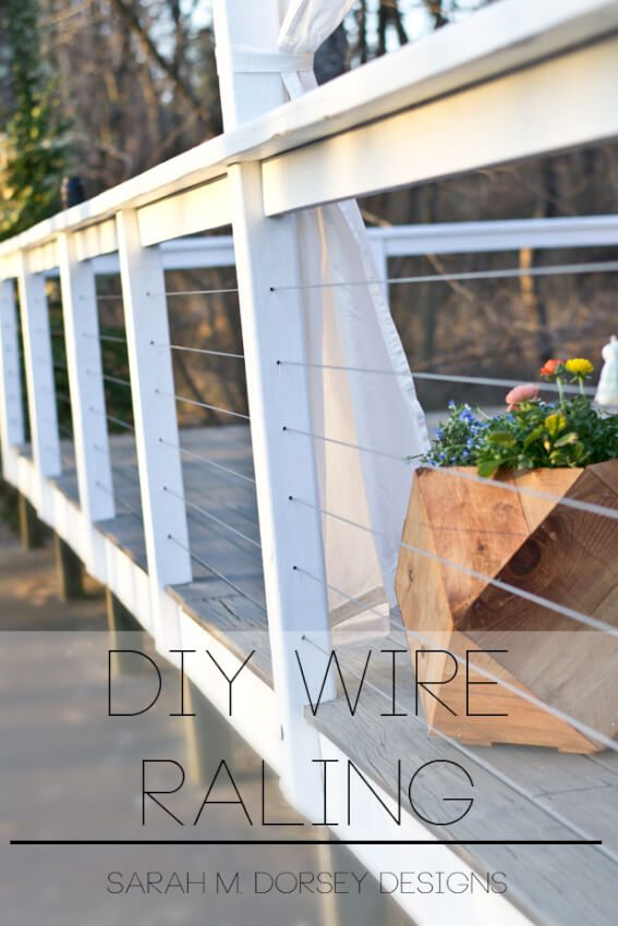 white wood and cable wire deck railing with wooden planter
