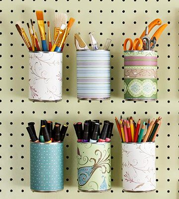peg board paintbrushes markers scissors decorated cans
