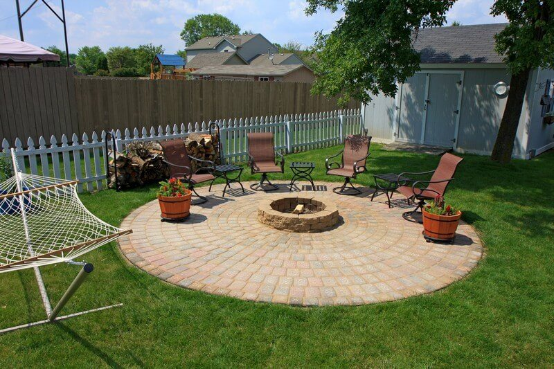 While more involved and expensive, this paving stone patio surrounding the fire pit makes for an incredible backyard space.