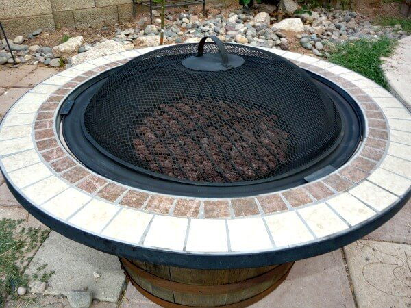 Unique fire pit that uses a halved whiskey barrel as the base and support for the pit.